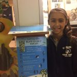 student with beach clean up banner